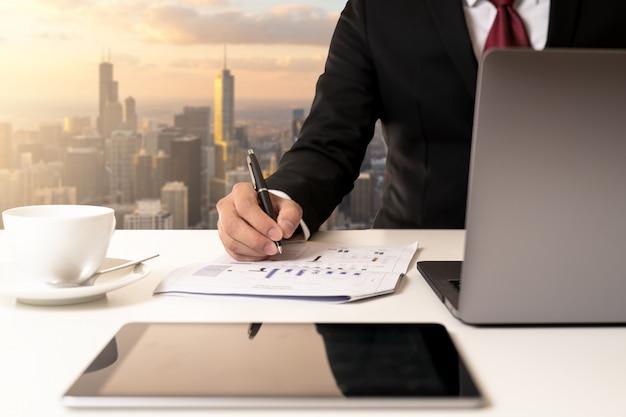 El empresario de la mano que sostiene la pluma y el análisis de datos de la carta en el documento de papel