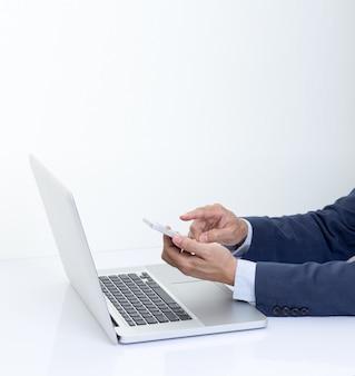 Empresario mano smartphone con computadora portátil