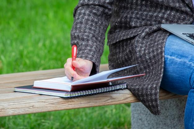 Empresario de mano trabajando con documentos en un banco de la calle