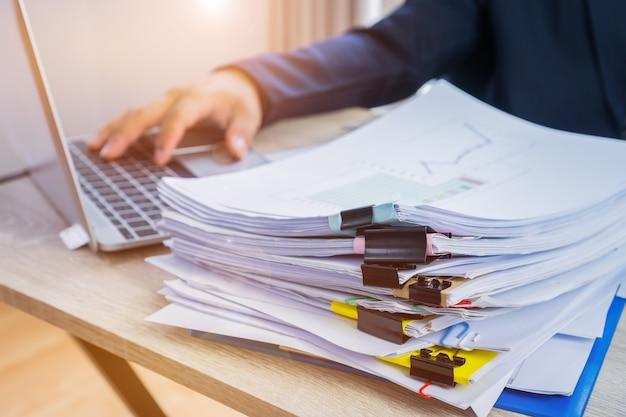 Empresario manos de datos de trabajo de computadora y pilas de archivos de papel en busca de información
