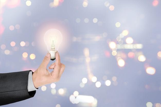 Empresario manos sosteniendo bombilla brillante como símbolo de idea creativa
