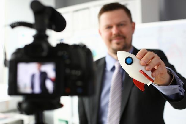 Empresario mantenga cohete en mano closeup