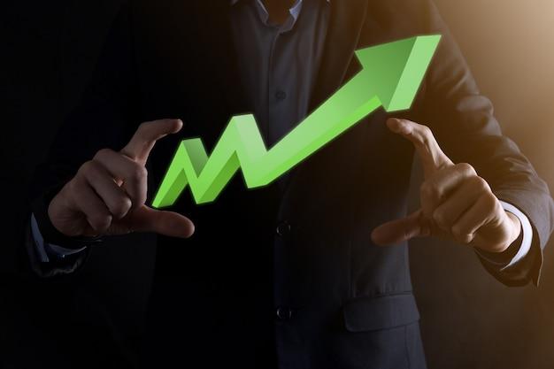 El empresario mantenga el dibujo en el gráfico de crecimiento de la pantalla, la flecha del icono de crecimiento positivo. apuntando al gráfico de negocios creativos con flechas hacia arriba. concepto de crecimiento financiero, empresarial.