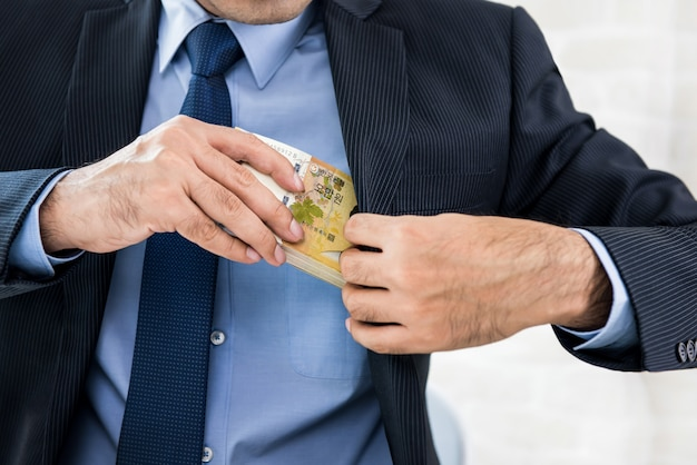Empresario manteniendo dinero, coreano ganó billetes, en el bolsillo de su traje