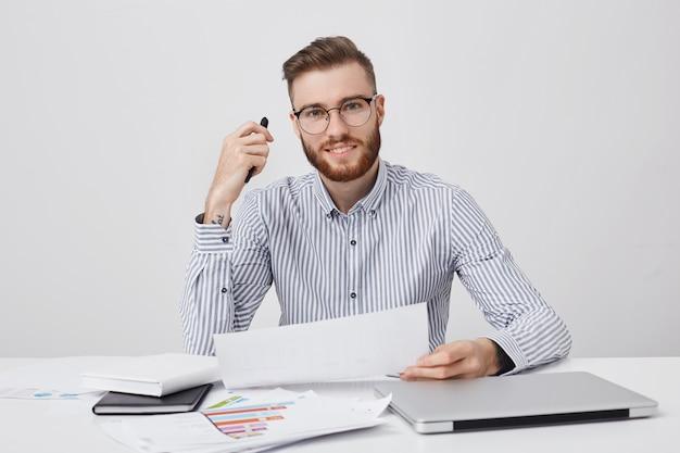 Empresario masculino profesional exitoso sostiene papel y bolígrafo, lee atentamente el contrato