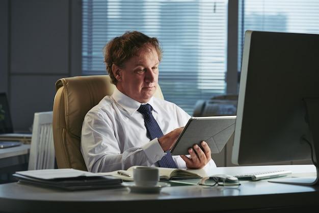 Empresario de mediana edad leyendo noticias globales en línea en su tablet pc