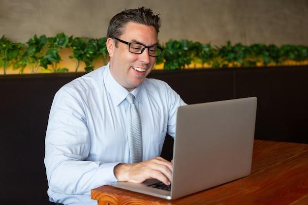Empresario de mediana edad positivo escribiendo en la computadora portátil