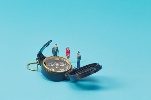 Empresario en miniatura y brújula en azul brillante