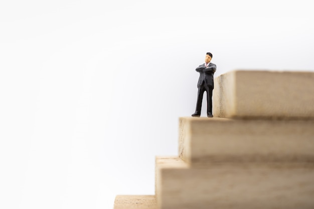 Empresario miniatura figura de pie en la pila de bloques de madera escalera pila de bloques de madera