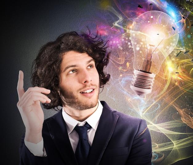Empresario mirando una bombilla dibujada y piensa en una nueva idea creativa