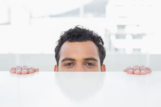 Empresario mirando a escondidas detrás del escritorio en la oficina