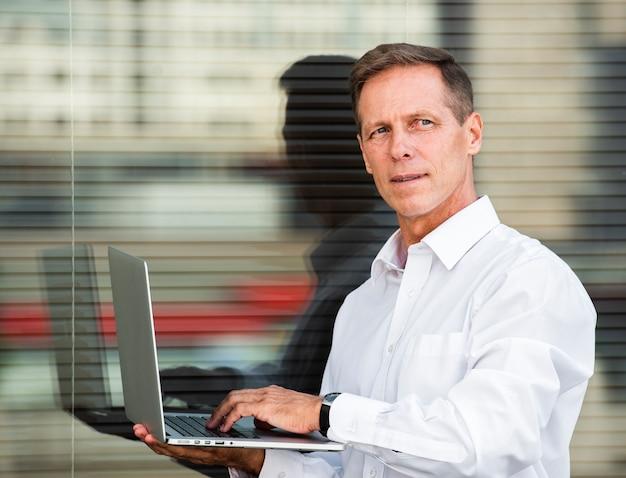 Empresario mirando lejos sosteniendo portátil