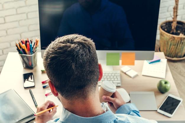 Empresario mirando el monitor de la computadora durante la jornada laboral en la oficina