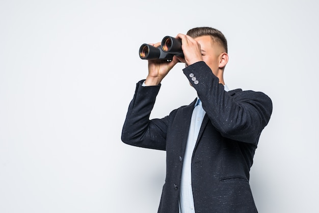 El empresario está mirando a través de un par de binoculares aislado en la pared blanca