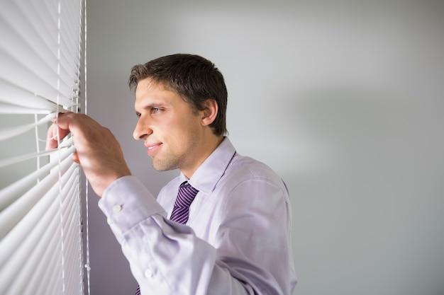 Empresario mirando a través de las persianas en la oficina