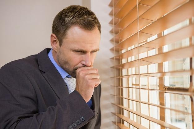 Empresario mirando por la ventana