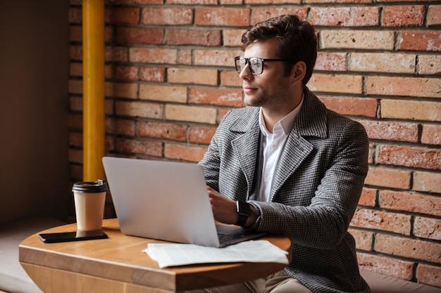 Empresario misterioso en anteojos sentado junto a la mesa en la cafetería con computadora portátil y apartar la mirada