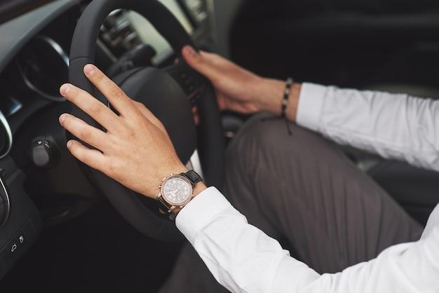 Un empresario monta su coche, se mueve sobre el volante. mano con reloj.