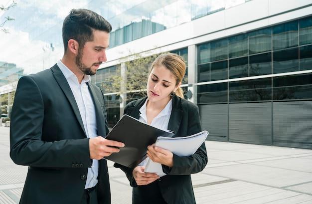 Empresario mostrando documentos a su colega de pie fuera de la oficina
