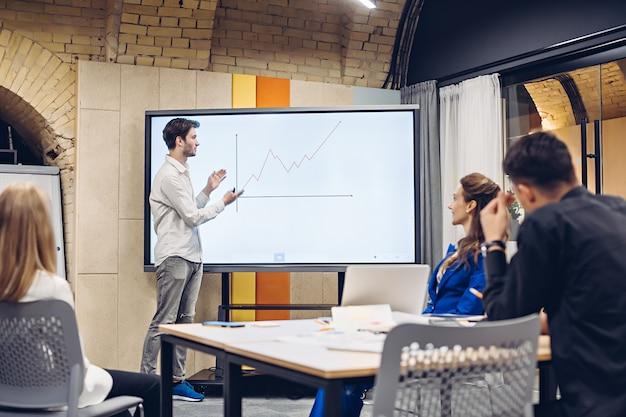 Empresario mostrando gráfico de crecimiento a colegas