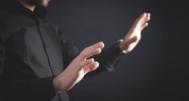 Empresario mostrando las manos vacías en la oscuridad.