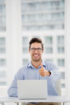 Empresario mostrando los pulgares hacia arriba mientras usa la computadora portátil