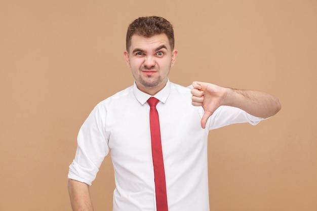 Empresario mostrando signo de aversión. concepto de gente de negocios, buenas y malas emociones y sentimientos. foto de estudio, aislado sobre fondo marrón claro