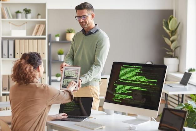 Empresario mostrando software en tablet pc a su colega mientras trabajan en el servicio informático