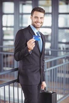 Empresario mostrando tarjeta de crédito mientras está parado en la oficina