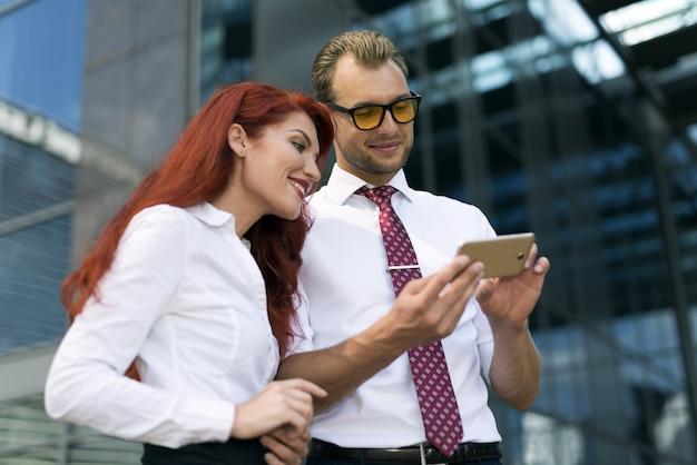 Empresario mostrando teléfono inteligente a un colega