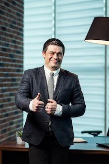 El empresario muestra un gesto como a mano, concepto de empresario, hombre mostrando el pulgar hacia arriba o como gesto como concepto de trabajo excelente y exitoso, retrato de businessmam