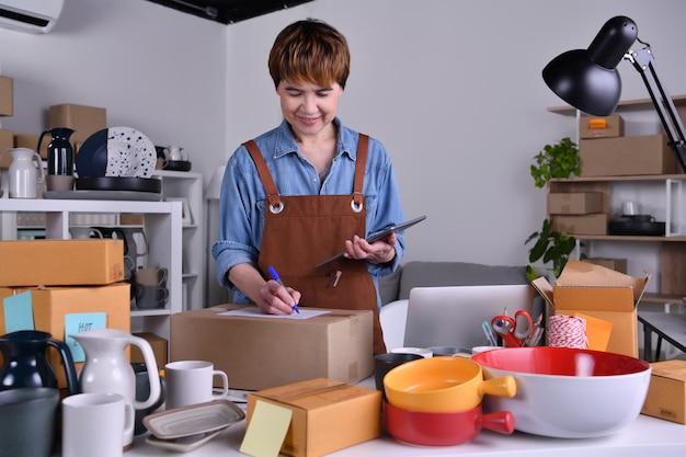 Empresario de mujer asiática madura, propietario de la empresa que comprueba la dirección y los detalles de la entrega antes de enviar el producto. trabajo de negocios de venta en línea en concepto de hogar