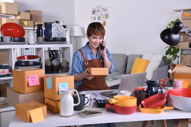 Empresario de mujer asiática madura, propietario de un negocio con teléfono inteligente que verifica la dirección y los detalles de la entrega antes de enviar el producto. trabajo de negocios de venta en línea en concepto de hogar
