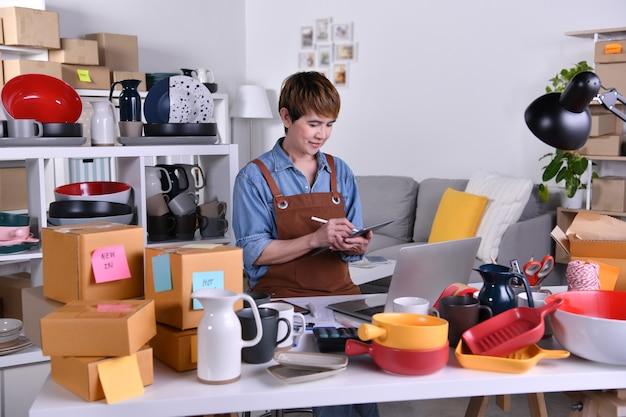 Empresario de mujer asiática madura, propietario de negocio trabajando en tableta digital. trabajo de negocios de venta en línea en concepto de hogar