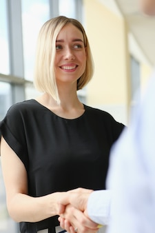 Empresario y mujer se dan la mano como hola en la oficina