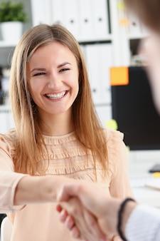 Empresario y mujer se dan la mano como hola