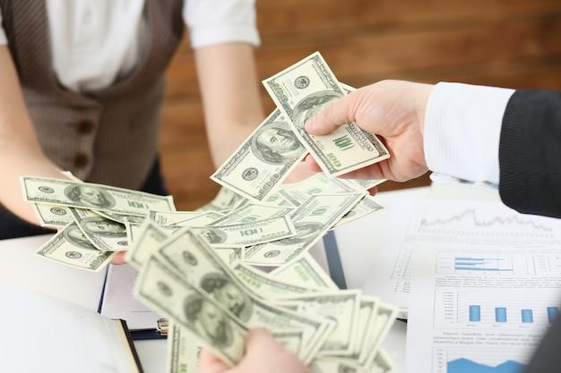 Empresario y mujer de negocios contando efectivo sobre la mesa en la oficina con manos salario de muchos dólares para el futuro cercano