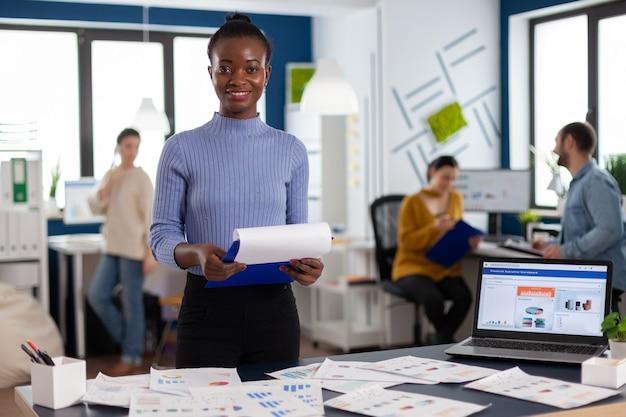 Empresario de mujer negra sonriente sosteniendo portapapeles con estrategia de empresa sonriendo a la cámara. equipo diverso de gente de negocios que analiza los informes financieros de la empresa desde la computadora.