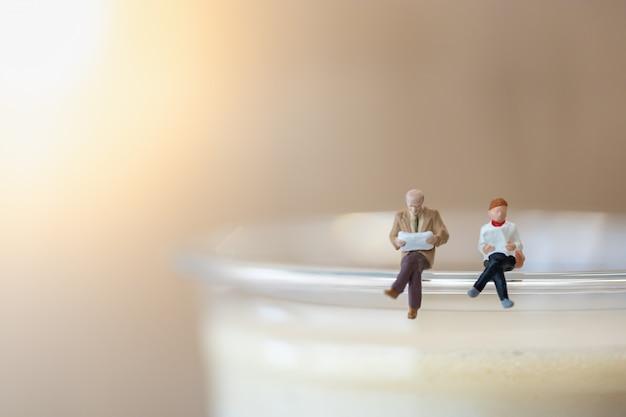 Empresario y mujer sentada y leyendo el libro en la parte superior de la taza de plástico de café con leche helado.
