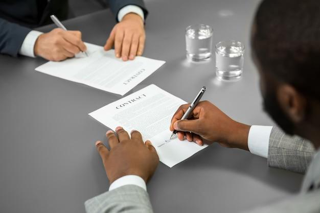 El empresario negro firma un contrato. bienvenidos a la empresa. jefe emplea a gerente. un candidato exitoso.
