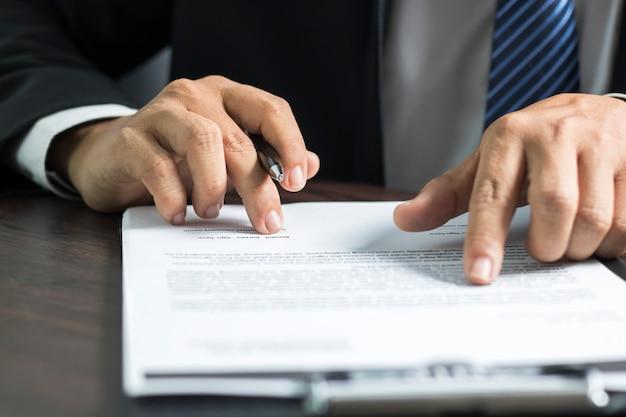Empresario o abogado leyendo y firmando en papel de contrato