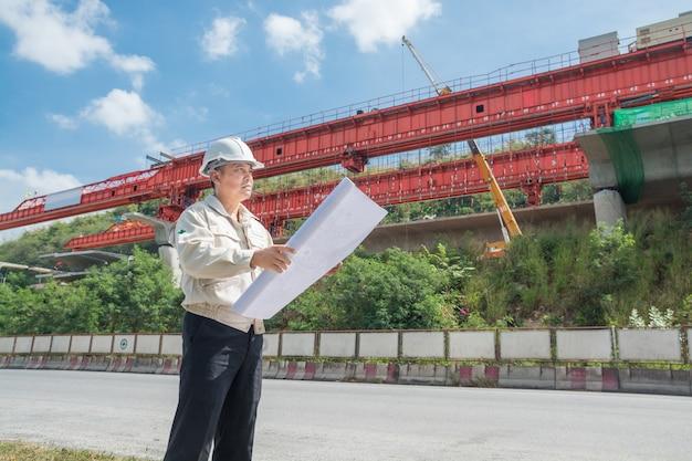 Empresario o ingeniero o arquitecto que lleva casco y chaleco de seguridad supervisa el proyecto de autopista o autopista