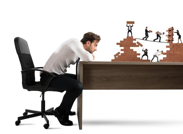 El empresario observa un trabajo en equipo de empresarios que trabajan juntos en una construcción de ladrillos