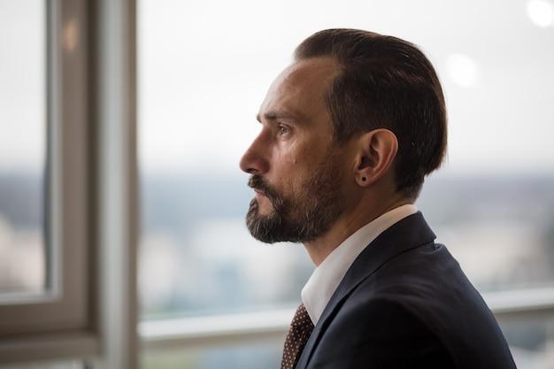 Un empresario en la oficina mirando por la ventana