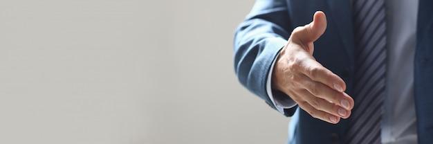 Empresario ofrece mano para estrechar como hola en primer plano de la oficina