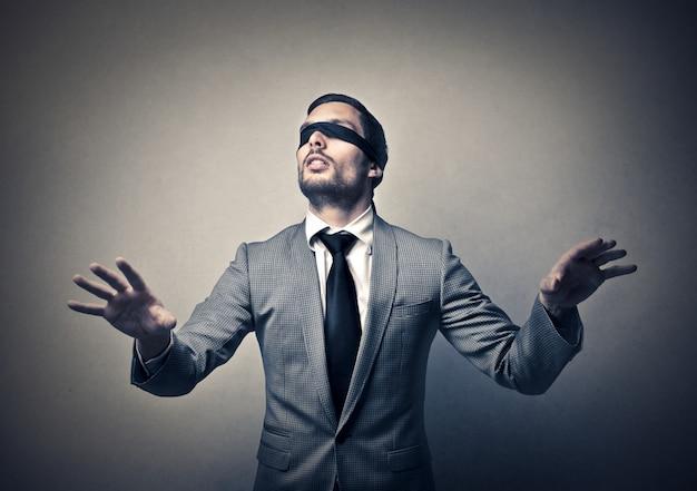 Empresario con los ojos vendados tratando de navegar