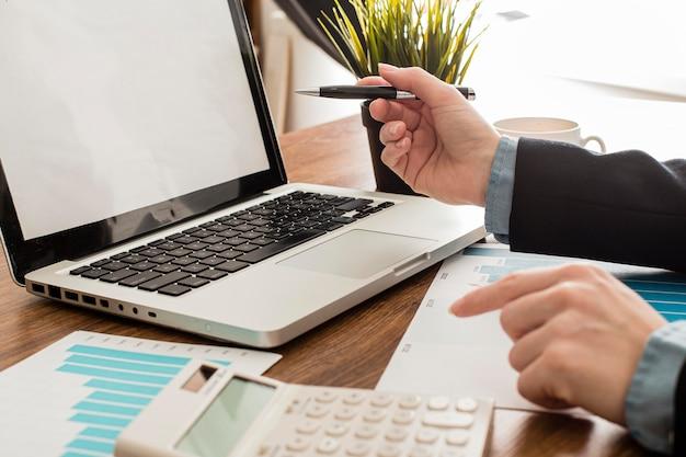 Empresario con ordenador portátil y calculadora en la oficina.