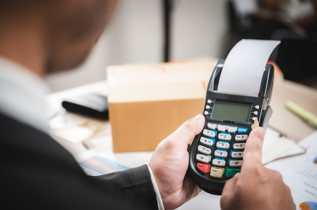 Empresario pagando con tarjeta de crédito con una máquina lectora de tarjetas de crédito, banca electrónica y concepto de marketing comercial en línea
