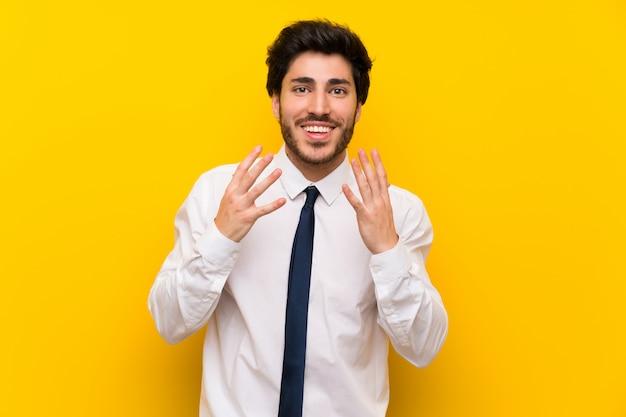 Empresario en pared amarilla aislada con expresión facial sorpresa