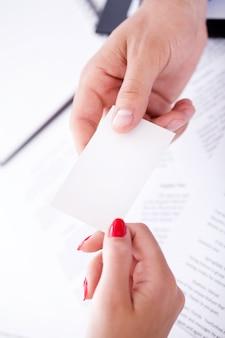 El empresario pasa la tarjeta de visita a su compañero